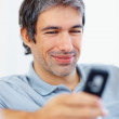 Smiling guy reading funny text message - Stok fotoraf