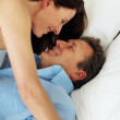 Mature couple sharing an intimate moment in bed - Foto Stock