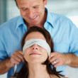 Smiling handsome man blindfolding his wife - Stock Photo