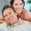 Portrait of a smiling middle aged couple relaxing at home - Stock Photo
