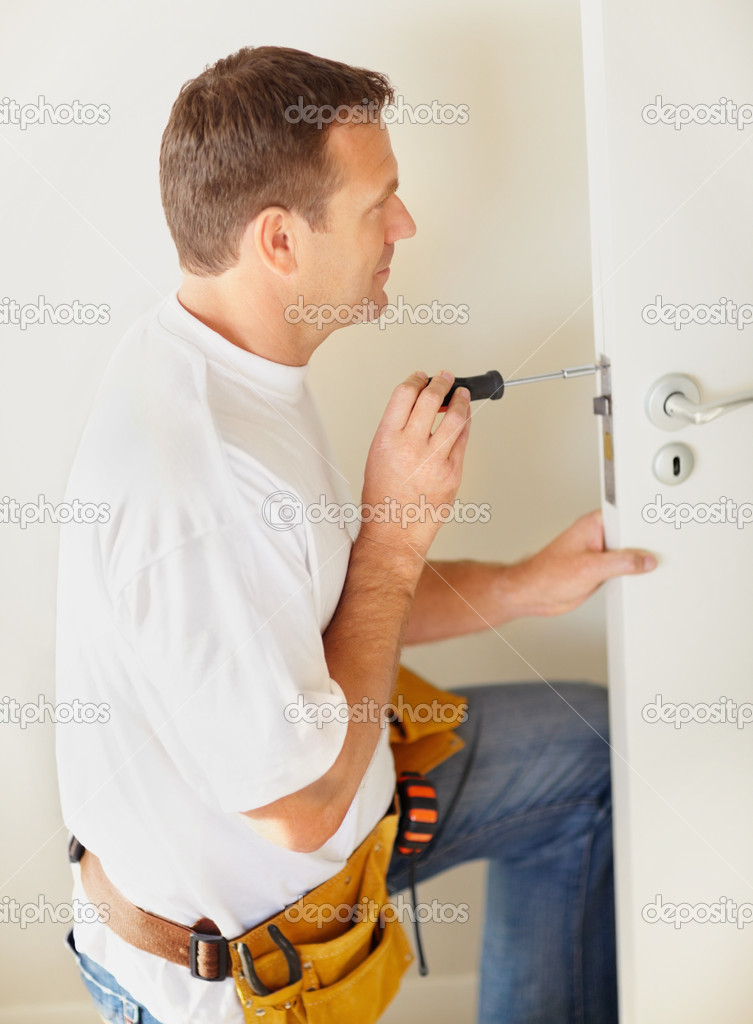 Mature carpenter attaching a lock to the door — Stock Photo #3457183