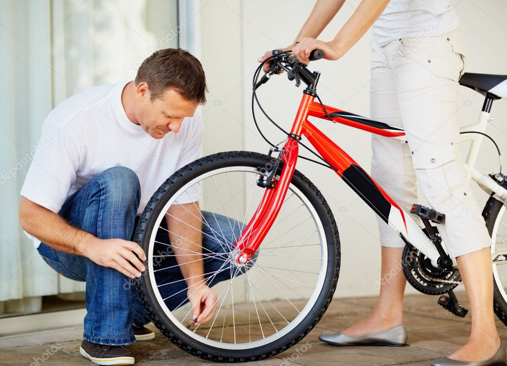 Husband checking the tyre pressure of his wife's new bicycle — Stock Photo #3457391