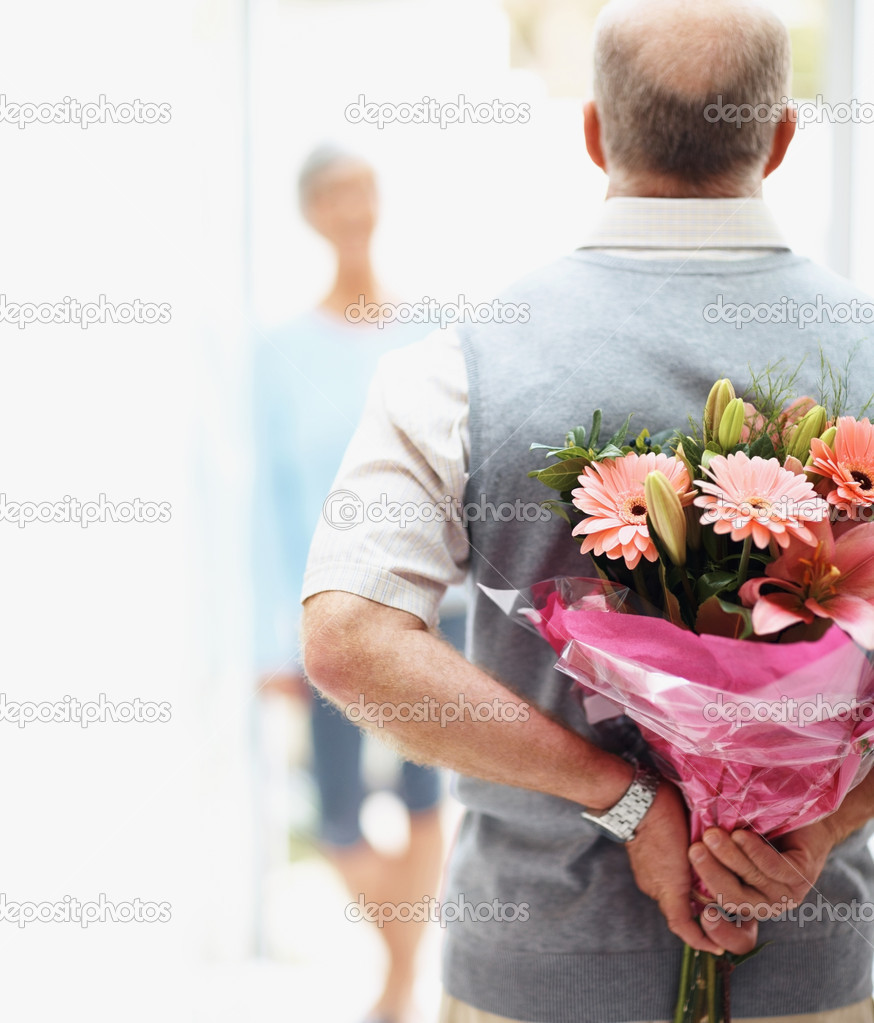 Closeup of a senior man hiding flowers before a woman  Stock Photo #3457577