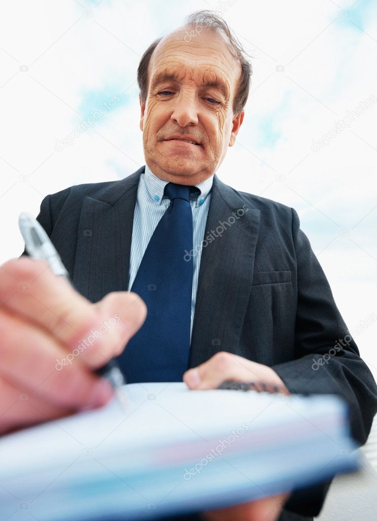 Busy senior business man taking notes on a book outdoors — Stock Photo #3458181