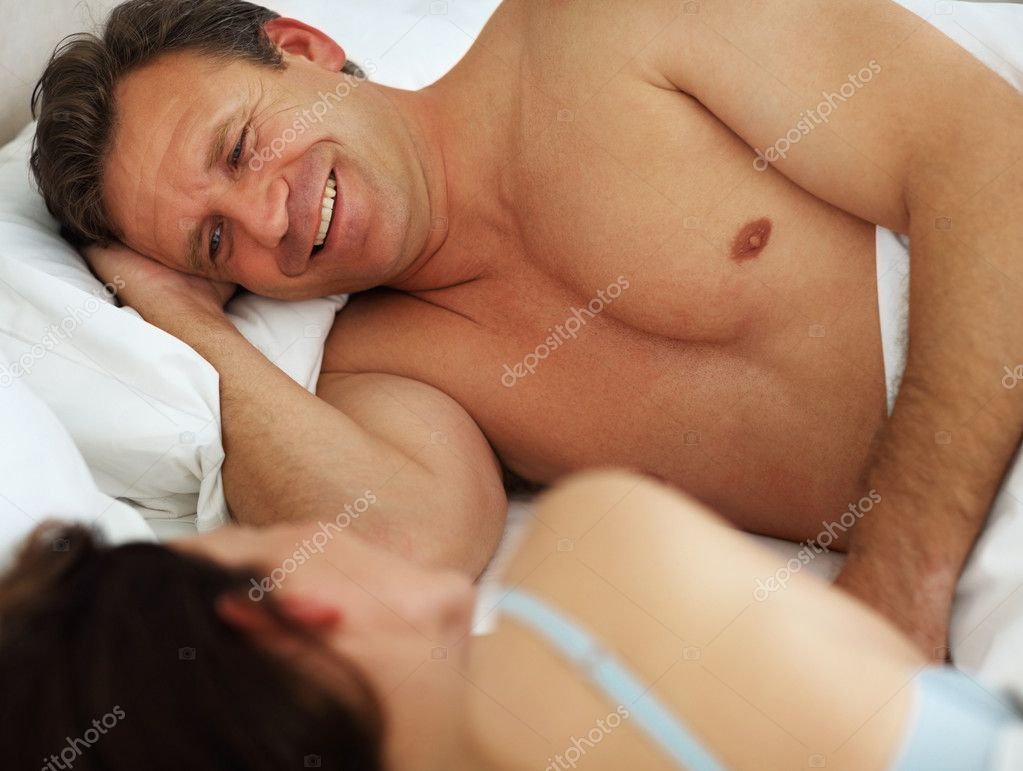 Handsome mature man lying besides wife in bed