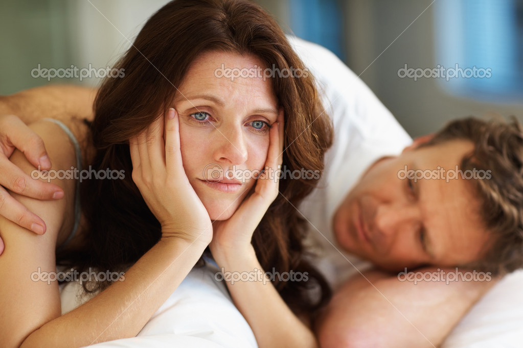 Sexual related problems - Middle aged woman lying on bed beside her husband in deep thought — Stock Photo #3459743