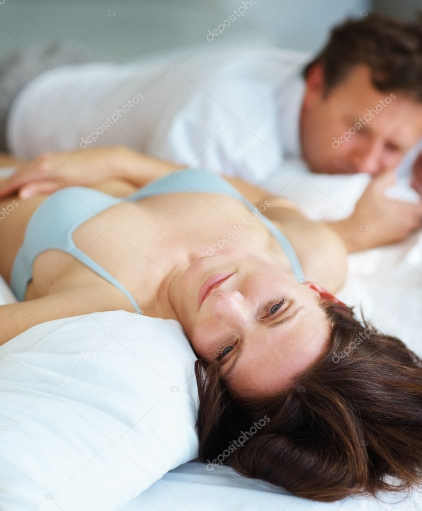 Sexual related problems - Mature woman lying on bed beside her husband in deep thought  Stock Photo #3459761