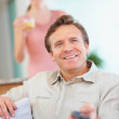 Royalty-Free Stock Photo: Smiling mature man holding remote with a woman in background