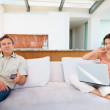 Man watching TV and woman working on the laptop at home - Stock Photo