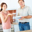 Happy mature couple during household chores in the kitchen - Stok fotoraf