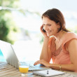 Royalty-Free Stock Photo: Happy mature woman using a laptop while on the phone