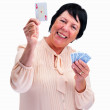 Royalty-Free Stock Photo: Smiling senior woman showing you an ace of hearts on white
