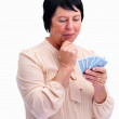 Royalty-Free Stock Photo: Thoughtful old woman playing cards against white