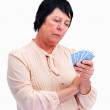 Royalty-Free Stock Photo: Thoughtful senior woman playing cards over white