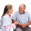 Royalty-Free Stock Photo: Happy nurse with a smiling senior man sitting on chair