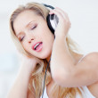 Royalty-Free Stock Photo: Cute woman enjoying to music over headphones