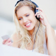 Royalty-Free Stock Photo: Happy young female listening to music over the headphones