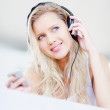 Royalty-Free Stock Photo: Beautiful happy female listening to music over headphones