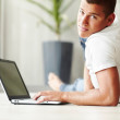 Smart young guy lying on floor and using laptop - Foto de Stock  
