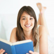 Charming young woman reading a novel - Stock Photo