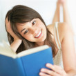 An attractive young female reading a book - Stock Photo