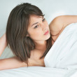 Thoughtful young female lying on the bed - Stock Photo