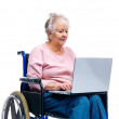 Royalty-Free Stock Photo: Senior woman sitting on a wheelchair with laptop