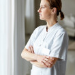 Middle aged nurse day dreaming outside the window - Stockfoto