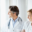 Doctor and nurse standing together and looking at copyspace - Stock Photo