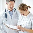 Happy mature medical staff making notes together - Stock Photo