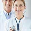 Royalty-Free Stock Photo: Happy nurse holding a stethoscope and doctor at the back