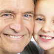 Grandfather and granddaughter smiling together - Stock Photo