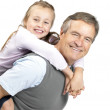 Little girl enjoying piggyback ride with her grandfather - Stock Photo