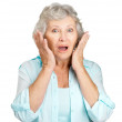 Surprised senior woman with hand on her cheeks - Stock Photo