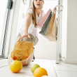 Returning from store - Female picking up fallen fruits at home - Stok fotoğraf