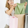 Happy woman with shopping bags looking at new top - Foto Stock