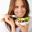 Pretty young lady looking away with fruit salad - Stock Photo