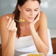 Woman eating cornflakes and reading magazine - Stock Photo