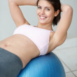 Healthy young female doing physical exercises on the ball - Stock Photo