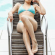 Young female on the deckchair by the swimming pool - Stock Photo