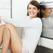 Cute female sitting on the floor by the oven with a smile - Stock Photo
