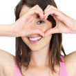 Royalty-Free Stock Photo: Cute woman making a heart shape with hands against white