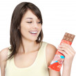 Royalty-Free Stock Photo: Smiling casual female holding a bar of chocolate