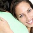 Closeup of a smiling female hugging a man - Stock Photo