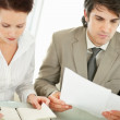 Young business doing their paperwork at the office - Stock Photo