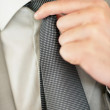 Closeup of a business man adjusting his tie - Stock Photo