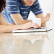 Royalty-Free Stock Photo: Cropped image of a couple using a laptop on the table