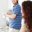 Royalty-Free Stock Photo: Young man doing the dishes and looking at female