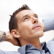 Handsome young man lost in deep thought - Stock Photo