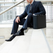Royalty-Free Stock Photo: Handsome businessman sitting on stairs outside a building